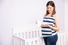 Schwangere Frau, die Baby-Kleidung betrachtet lizenzfreie stockfotos