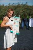 Schwangere Frau, die Babykleidung hält Stockbilder