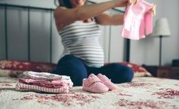 Schwangere Frau, die Babywolljacke schaut lizenzfreie stockfotos