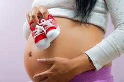 Schwangere Frau, die Bauch zur Kamera zeigt Stockbild