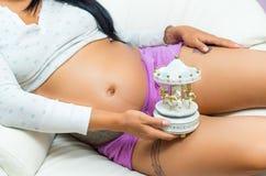 Schwangere Frau, die Bauch zur Kamera zeigt Stockfoto
