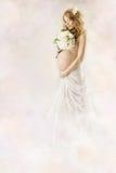Schwangere Frau, die Blumen im weißen Kleid betrachtet. Stockbilder