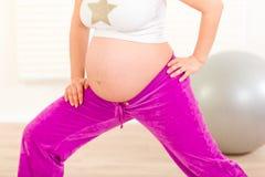 Schwangere Frau, die Übungen ausdehnend tut. Nahaufnahme Lizenzfreie Stockfotos