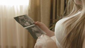 Schwangere Frau, die das Echographiebild des zukünftigen Baby ` s betrachtet stock video