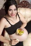 Schwangere Frau, die den Baby-Stuhl isst Schüssel-frische Frucht erwartet Stockfotos