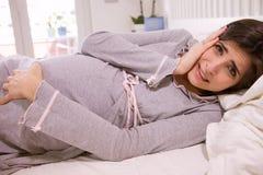 Schwangere Frau, die in den Bettgefühlsschmerz schauen Kamera liegt stockfoto