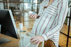 Schwangere Frau, die den netten Verlobungsring nimmt Vitamine trägt lizenzfreies stockfoto