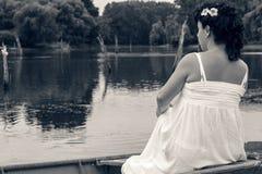 Schwangere Frau, die in der Natur nahe See genießt Stockbild