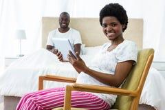 Schwangere Frau, die digitale Tablette auf Stuhl und den Mann sitzt auf Bett verwendet Stockbilder
