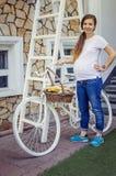 Schwangere Frau, die draußen mit weißem Fahrrad aufwirft stockbild