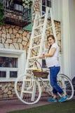 Schwangere Frau, die draußen mit weißem Fahrrad aufwirft stockfotografie