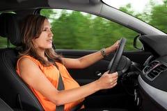 Schwangere Frau, die ein Auto antreibt Stockfotos
