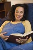 Schwangere Frau, die ein Buch liest Stockfotografie