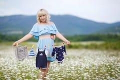 Schwangere Frau, die ein Seil mit Kleidung hält Lizenzfreie Stockfotografie