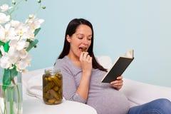 Schwangere Frau, die eine in Essig eingelegte Essiggurke isst. stockbilder