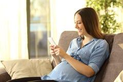 Schwangere Frau, die an einem Handy simst lizenzfreies stockfoto