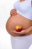 Schwangere Frau, die einen Apfel in ihren Händen anhält Diät, Vitamine und gesundes Lebensmittel während der Schwangerschaft Lizenzfreies Stockbild