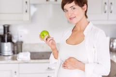 Schwangere Frau, die einen Apfel isst Lizenzfreie Stockfotografie