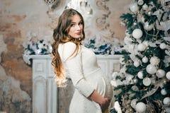 Schwangere Frau, die einen Bauch nahe einem Weihnachtsbaum mit Lichtern hält Lizenzfreies Stockbild