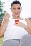 Schwangere Frau, die einen gesunden Imbiss, Fruchtjoghurt isst Lizenzfreies Stockfoto