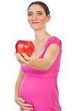 Schwangere Frau, die einen großen roten Apfel gibt Stockfoto