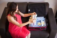 Schwangere Frau, die einen Koffer verpackt Stockfotos