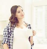 Schwangere Frau, die einen Tee in der Küche trinkt Stockfoto