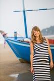 Schwangere Frau, die entlang einen Strand geht Stockfoto