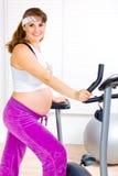 Schwangere Frau, die für Training auf Fahrrad sich vorbereitet Stockfotos