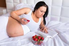Schwangere Frau, die frische Erdbeeren isst Lizenzfreies Stockfoto