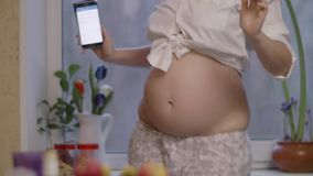 Schwangere Frau, die glücklich ist und zu Hause zur Mobiltelefonmusik tanzt stock video footage