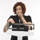 Schwangere Frau, die ihr Gewicht überprüft. Lizenzfreie Stockfotos