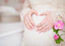 Schwangere Frau, die ihre Hände in einer Herzform auf ihrem Bauch hält Stockbilder