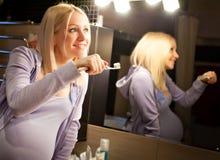Schwangere Frau, die ihre Zähne säubert Stockbild