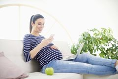 Schwangere Frau, die an ihrem Handy spricht und Notizbuch verwendet Lizenzfreie Stockfotografie