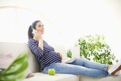 Schwangere Frau, die an ihrem Handy spricht und Notizbuch verwendet Stockbilder