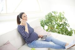 Schwangere Frau, die an ihrem Handy spricht und Notizbuch verwendet Stockfoto