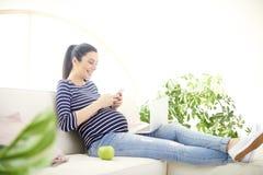Schwangere Frau, die an ihrem Handy spricht und Notizbuch verwendet Stockbild
