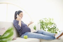 Schwangere Frau, die an ihrem Handy spricht und Notizbuch verwendet Stockfotografie