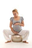 Schwangere Frau, die ihren Bauch bewundert Lizenzfreie Stockfotos
