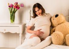Schwangere Frau, die ihren Bauch hält Stockbild