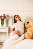 Schwangere Frau, die ihren Bauch hält Stockfotografie