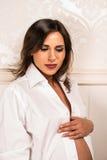 Schwangere Frau, die ihren Bauch hält Stockfotos