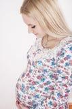Schwangere Frau, die ihren Bauch umarmt Lizenzfreie Stockfotografie