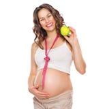 Schwangere Frau, die ihren dicken Bauch misst und Apfel isst Lizenzfreie Stockfotos