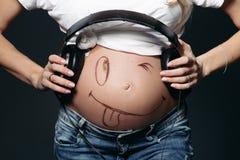 Schwangere Frau, die ihren nackten Bauch mit Lächeln zeigt und Kopfhörer hält lizenzfreie stockfotos
