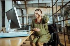 Schwangere Frau, die im Bürogefühl schrecklich und besorgt sitzt stockfotografie