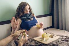 Schwangere Frau, die im Bettkranken mit Kälten und Grippe liegt Frau lehnt Medikation in den Pillen sich bilden beim Interessiere lizenzfreies stockfoto
