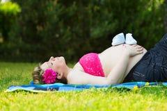 Schwangere Frau, die im grünen Gras liegt Stockfotografie