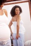 Schwangere Frau, die im Spiegel schaut Stockfoto